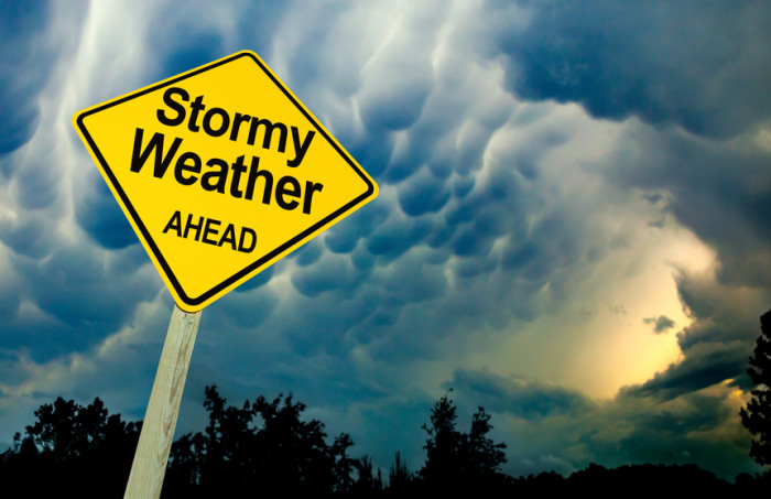 Stormy Weather Ahead Road Sign Against Dark Ominous Sky