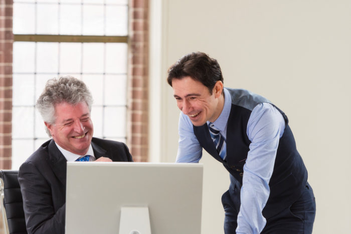 Color image of a manager and younger employee discussing about good business news in front of a computer. Copy space above.