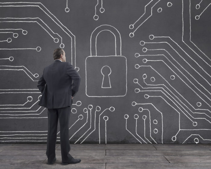 Cyber security concept: Rear view of businessman standing on wooden floor with circuit board and padlock sketched (chalk drawing) on the wall.