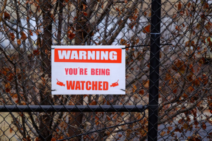 A waning sign for video cameras on a fence.
