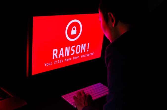 Computer screen with ransomware attack file encrypted alerts in red and a man in suit keying on keyboard in a dark room, ideal for online security and digital crime