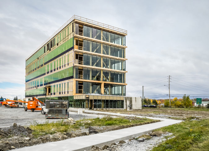 Saint-Hyacinthe, Сanada - October 24, 2016: SYNERGIA COMPLEX Built at the corner of Casavant Boulevard and East Johnson Street, Saint-Hyacinthe. The tower at prestigious offices will be built according to strict standards of sustainable development and seeks LEED certification. The building with modern architecture present an apparent wood structure as well as imposing fenestration, allowing access to natural light and great views.