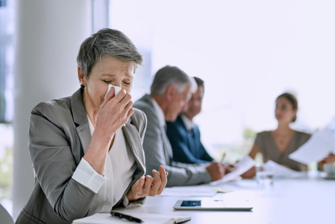 Cropped shot of a sick businesswoman blowing her nose in the boardroom
