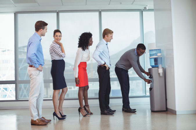 Business people standing in line by water cooler at office
