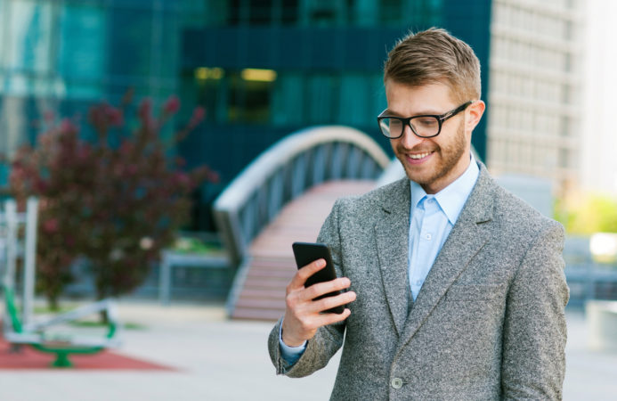 Young businessman using a smartphone with smile on his face