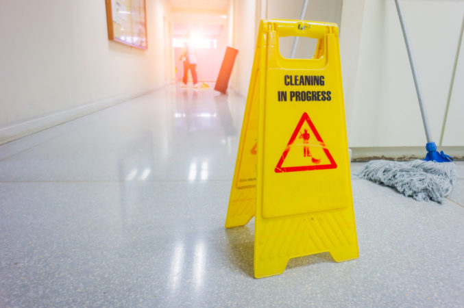 caution wet floor warning sign with blurred worker mopping floor.