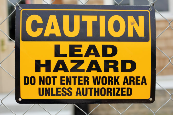 A caution sign warning of a lead hazard. Lead is a heavy metal and potentially hazardous to human health.