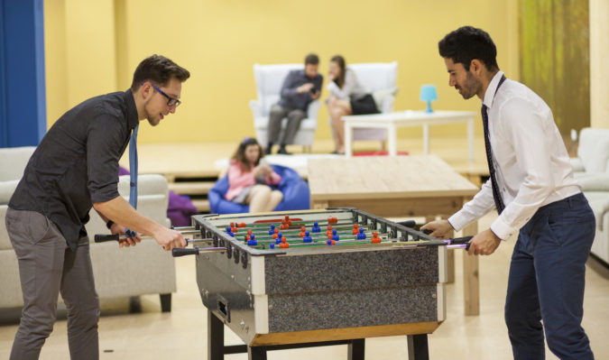 Businessmen playing table football with other coworkers in the background. Creative office space.