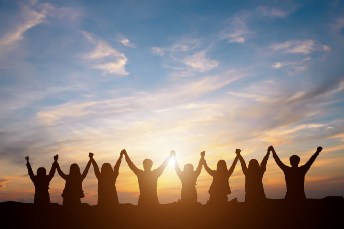 Silhouette of happy business team making high hands in sunset sky background for business teamwork concept