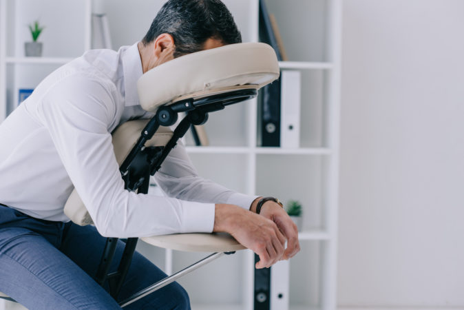businessman sitting in massage chair at office