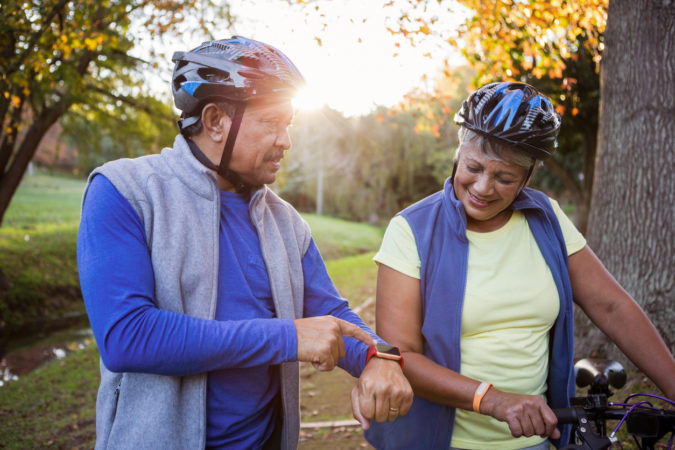 Man pointing his smart watch front of his wife in a park