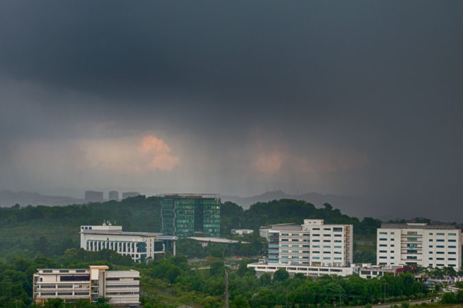 View of approaching rain storm, rainy clouds over the city, poor weather forecast.  Malaysia, Cyberjaya. Tropical cyclone in asia.
