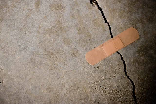 Adhesive bandage holding together a splitting concrete wall. (Concept: termporary solution) Tight/shallow DOF on bandage. (Adhesive bandage holding together a splitting concrete wall. (Concept: termporary solution) Tight/shallow DOF on bandage., ASCII