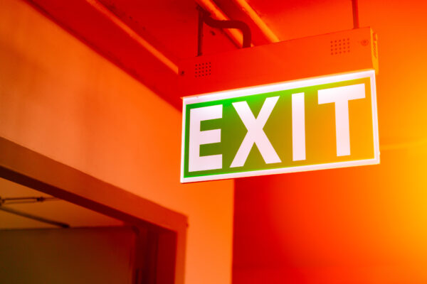 green fire exit sign light at emergency escape door