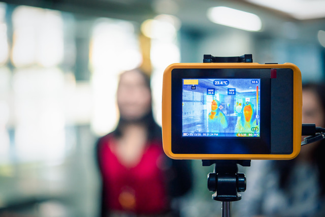 Asian people waiting for body temperature check before access to building for against epidemic flu covid19 or corona virus from wuhan in office by thermoscan or infrared thermal camera (Asian people waiting for body temperature check before access to